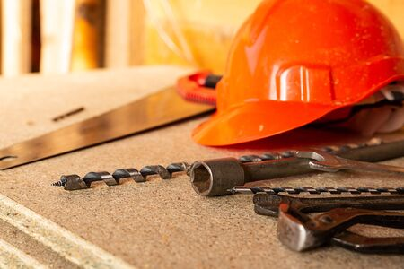 Foto de construction design pattern orange plastic helmet, set of drill drills and wire cutters lie on a light wooden background - Imagen libre de derechos