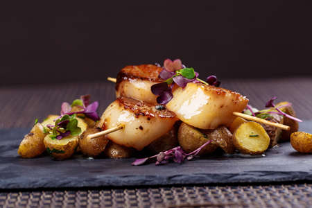 Photo pour Grilled scallops with roasted young potatoes - image libre de droit