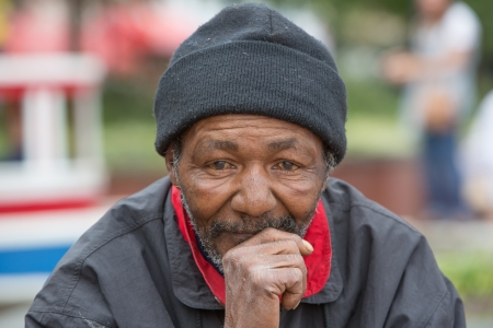 Foto de Portrait of homeless man thinking while sitting outdoors during the daytime - Imagen libre de derechos
