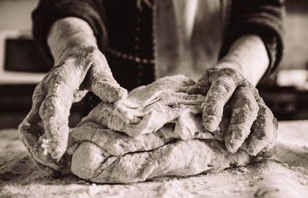 Photo for old italian grandma making pasta in the kitchen sepia effect - Royalty Free Image