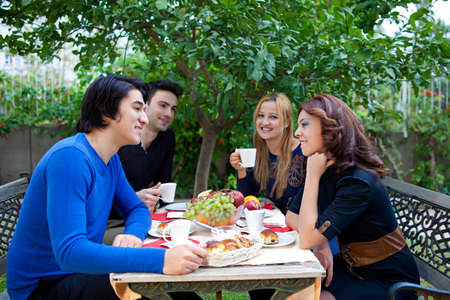 Two young students flirting while enjoying coffee at an outdoor venue much to the amusement of their friends at the table