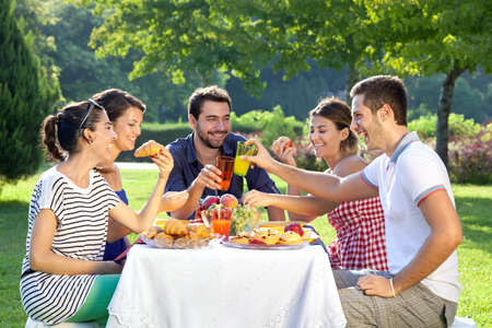 Photo for Friends enjoying a relaxing picnic sitting together laughing and chatting at a table in a lush green park - Royalty Free Image