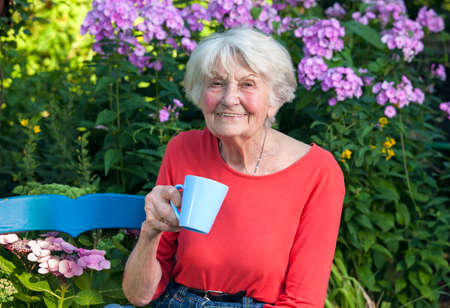 Foto de Close up Happy Grandma in Red Shirt Having a Cup of Coffee at the Garden with Flower Plants at the Background. - Imagen libre de derechos