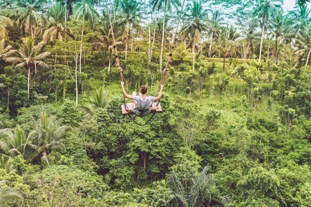 Photo for Young tourist woman swinging on the cliff in the jungle rainforest of a tropical Bali island. - Royalty Free Image