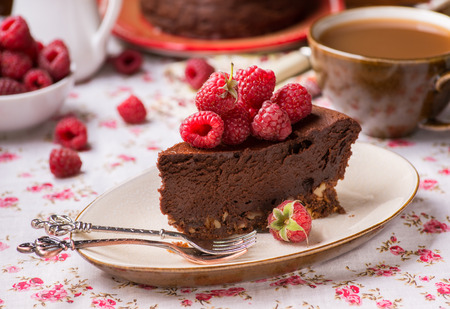 Photo pour Homemade chocolate cake with raspberry on plate, cup of coffee and barries on side, selective focus - image libre de droit