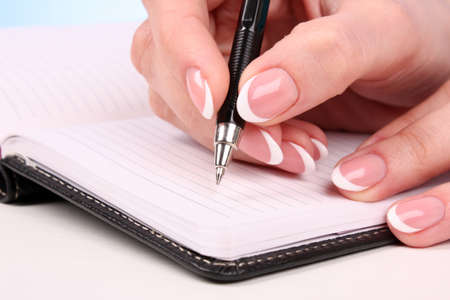woman hand writting in the notebook on table
