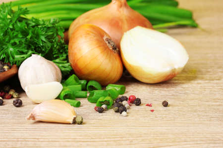 spices, onion, garlic and parsley on a wooden background
