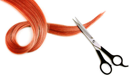 Shiny red hair and hair cutting shears isolated on white