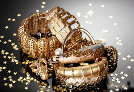 Foto de Beautiful golden jewelry on grey background - Imagen libre de derechos