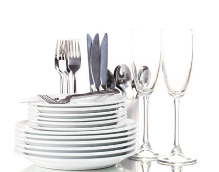 Clean plates, glasses and cutlery isolated on white