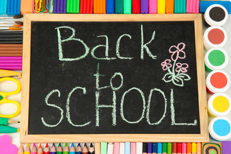 The words \'Back to School\' written in chalk on the small school desk with various school supplies close-up