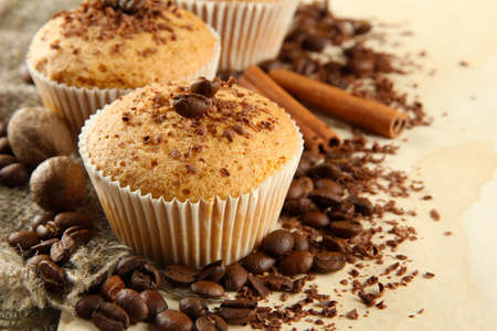 Photo for tasty muffin cakes with chocolate, spices and coffee seeds, on beige background - Royalty Free Image