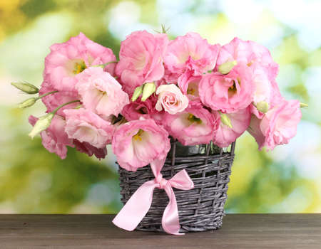 Foto de bouquet of eustoma flowers in  wicker vase, on wooden table, on green background - Imagen libre de derechos