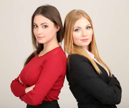 Two business women on grey background