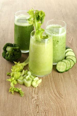 Glasses of green vegetable juice on wooden background