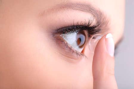 Foto de Young woman putting contact lens in her eye close up - Imagen libre de derechos