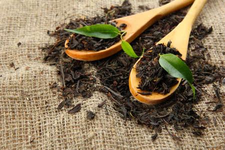 Foto de Dry tea with green leaves in wooden spoons, on burlap background - Imagen libre de derechos