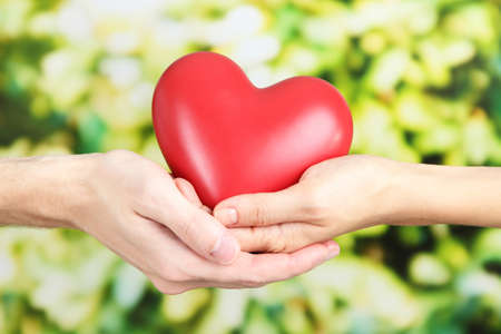 Foto de Heart in hands on nature background - Imagen libre de derechos