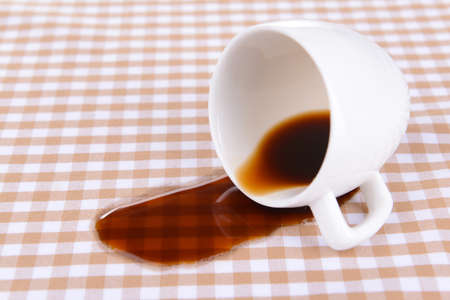 Photo pour Overturned cup of coffee on table close-up - image libre de droit