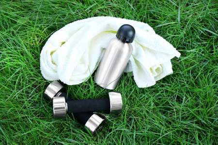 Dumbbells and bottle with water, towel on green grass background