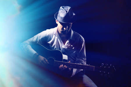 Photo for Young musician playing acoustic guitar, on dark background - Royalty Free Image