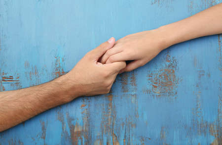 Foto de Loving couple holding hands close-up on wooden background - Imagen libre de derechos