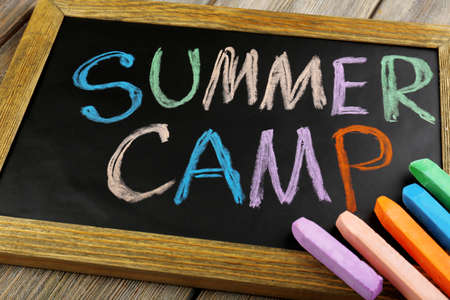 Text Summer camp written with chalk on chalkboard, and some chalk sticks of different colors
