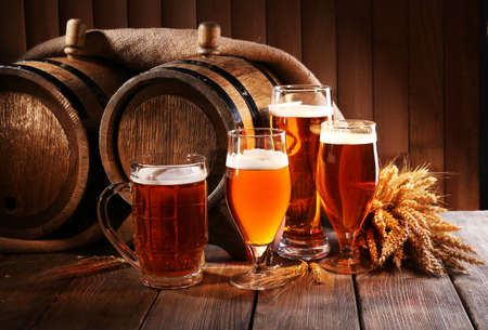 Foto de Beer barrel with beer glasses on table on wooden background - Imagen libre de derechos