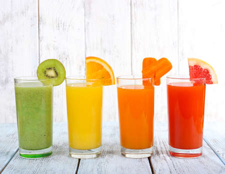 Photo pour Fruit and vegetable juice in glasses and pieces of fresh fruits on wooden table on wooden wall background - image libre de droit