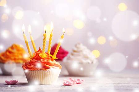 Photo pour Delicious birthday cupcakes on table on light festive background - image libre de droit