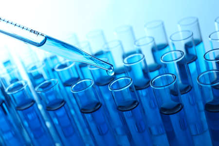 Foto de Pipette adding blue fluid to the one of test-tubes on light background - Imagen libre de derechos