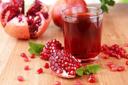 Photo pour Ripe pomegranates with juice on table close-up - image libre de droit