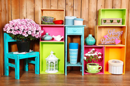 Foto de Beautiful colorful shelves with different home related objects on wooden wall background - Imagen libre de derechos