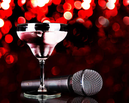 Photo for Silver microphone and cocktail on table on red lights background - Royalty Free Image