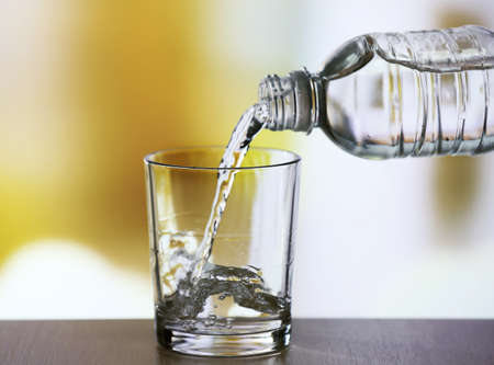Photo for Pouring water from bottle on  glass on light background - Royalty Free Image
