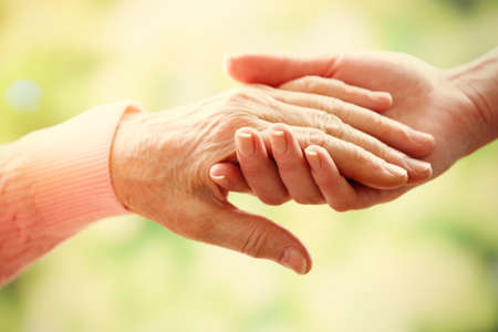 Foto de Old and young holding hands on light background, closeup - Imagen libre de derechos