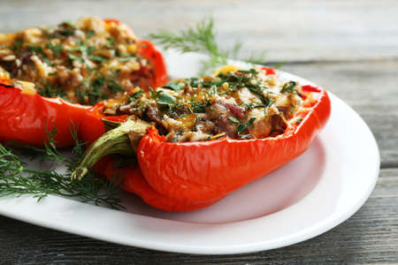 Photo for Stuffed red peppers with greens on plate on wooden table - Royalty Free Image