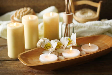 Foto de Composition of spa treatment, candles in bowl with water on wooden background - Imagen libre de derechos