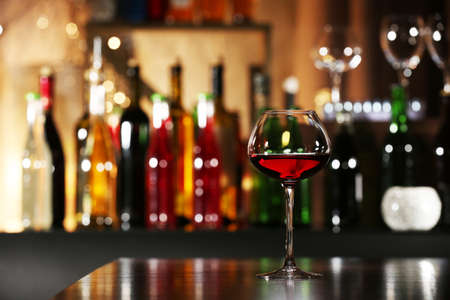 Photo for Glass of wine with bar on background - Royalty Free Image