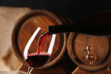 Photo pour Pouring red wine from bottle into glass with wooden wine casks on background - image libre de droit