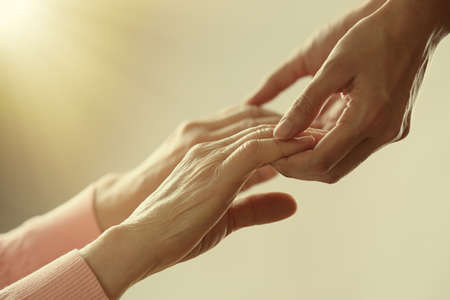 Photo for Old and young holding hands on light background, closeup - Royalty Free Image