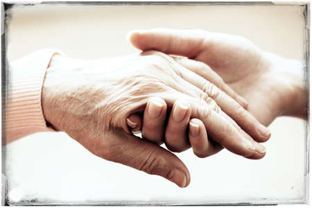 Foto de Old and young holding hands on light background, closeup - Imagen libre de derechos