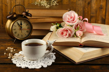 Photo pour Cup of tea with books and flowers on wooden background - image libre de droit