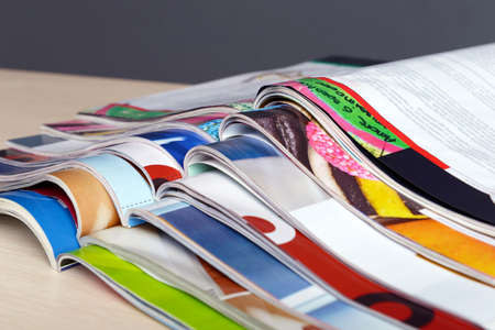 Foto de Magazines on wooden table on gray background - Imagen libre de derechos