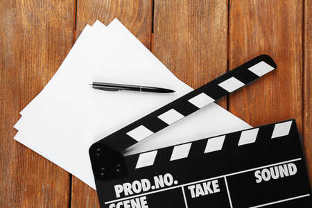 Photo for Movie clapper with sheets of paper and pen on wooden planks background - Royalty Free Image