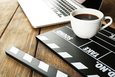 Photo for Movie clapper with laptop and cup of coffee on wooden background - Royalty Free Image