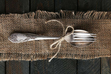 Photo for Silverware tied with rope on burlap cloth and wooden planks background - Royalty Free Image