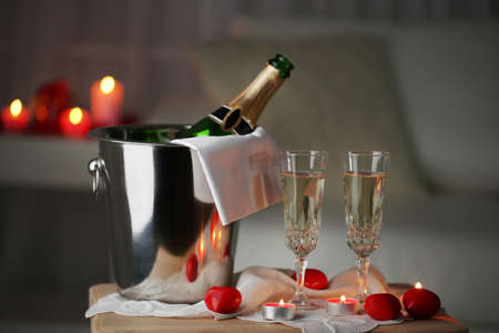Foto de Champagne glasses and rose petals for celebrating Valentines Day, on dark background - Imagen libre de derechos