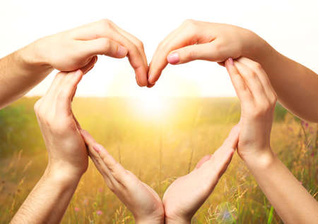 Foto de Heart shaped by hands on nature background - Imagen libre de derechos