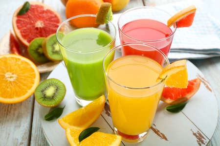 Photo pour Fresh juices with fruits on wooden table - image libre de droit